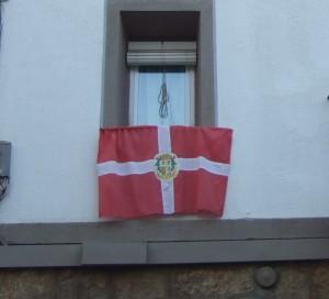 Una bandera de Caspe tapando la placa, antes de ser inaugurada